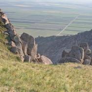Contrast intre culmea stancoasa si campurile de la baza muntelui - Culmea Pricopanului, Muntii Macin